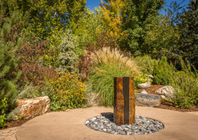 Cored boulder Water Feature, Custom Patio, Ornamental Planting Beds